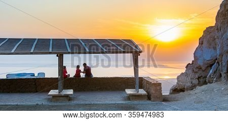 Family Admiring A Beautiful Sunrise On The Dead Sea.