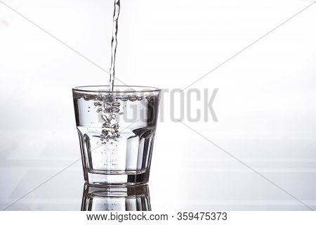 Pure Drinking Water In A Glass Cup. A Stream Of Water And Transparent Droplets On The Wall Of The Gl