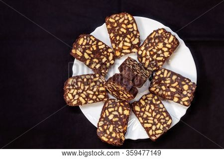 On A Black Background, A White Plate With Homemade Sweet Cookies Made Of Cocoa, Sugar, Walnuts, And