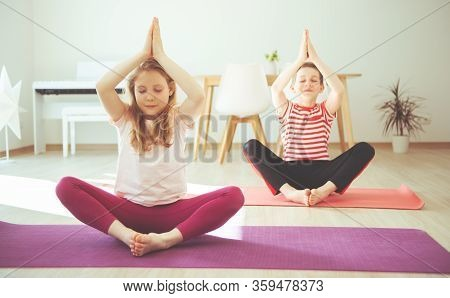 Cute Teenager Children Making Yoga At Home During Coronavirus Quarantine