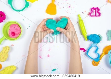 Little Girl Hands Close Up Playing With Colorful Modeling Clay On White Background. Home Education G