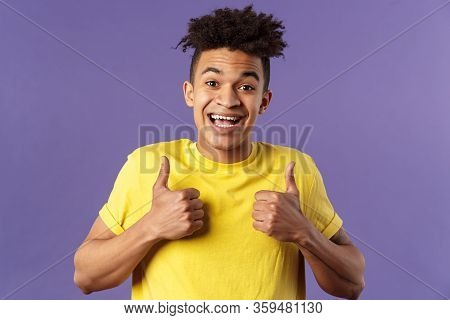 Close-up Portrait Of Enthusiastic Healthy Hispanic Guy Staying Positive, Show Thumbs-up And Smiling,