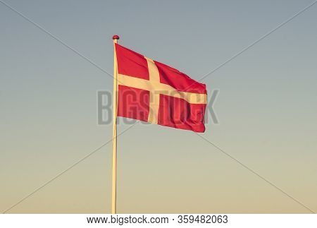 Danish Flag At Dawn Waving In The Wind In The Sunset On A Sunny Evening