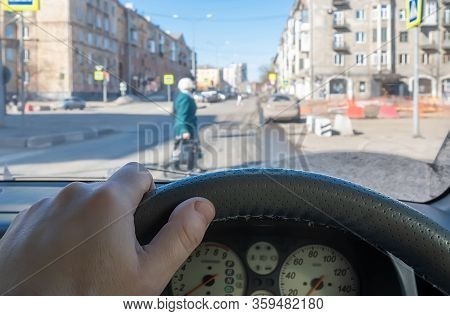 View From The Car, The Driver Hand On The Steering Wheel Of The Car, Located Opposite The Pedestrian