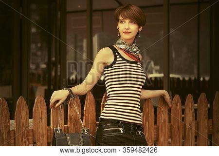Happy young fashion woman with handbag leaning on fence Stylish female model in striped tank top and denim skirt