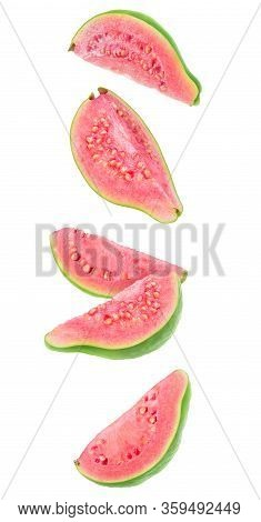 Guava Fruit Pieces In The Air. Five Slices Of Fresh Guava With Pink Flesh Falling Over White Backgro