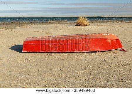 Red Boat Lies On The Shore Of Lake Kamyslybas, Large Saltwater Lake In The Kyzylorda Region Of Kazak