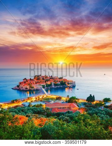 Exotic sundown over the small islet Sveti Stefan. Location place Montenegro, Adriatic sea, Europe. Image of most popular european travel destination. Holiday concept. Discover the beauty of earth.