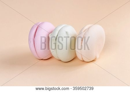 Delicious marshmallows in pastel colors on a beige background