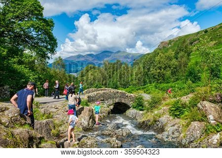 LAKE DISTRICT,ENGLAND - AUGUST 8,2019 : Tourists visiting the old Ashness Bridge on the Lake District