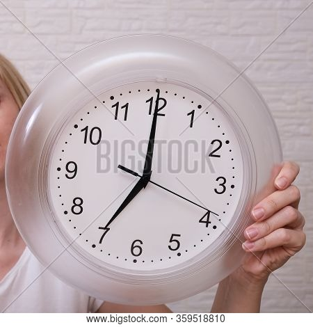 Woman Holding Clock Showing 7 Am In The Morning, Punctuality And Discipline Concept
