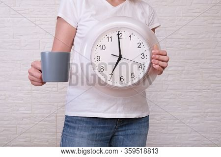Woman Freelancer With Clock Showing 7 Am And A Cup Of Coffee, Punctuality During Remote And Distant
