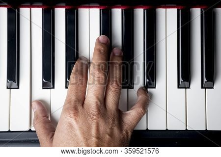 Right Hand Playing A A Minor Inversion Chord On The Piano