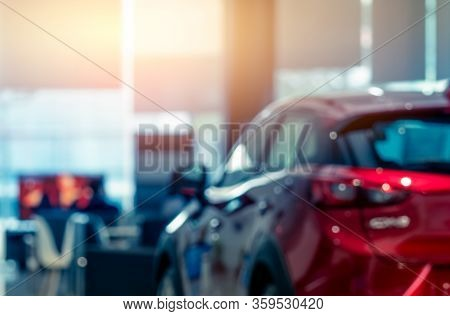 Blurred Rear View Of Red Car. Luxury Car Parked In Modern Showroom. Car Dealership Office. Automobil