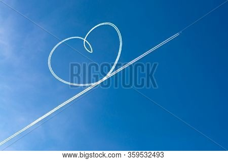 Airplane Flying Through Clear Blue Sky Left Heart Shape Of Vapour Trails Behide. Heart Shapes On The