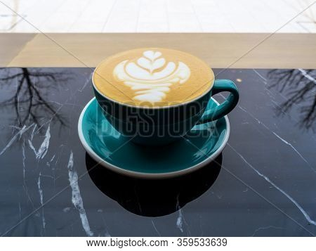 A Green Mug Of Cappuccino Sits On A Black Marble Table. Cappuccino In The Early Cold Morning. Reflec