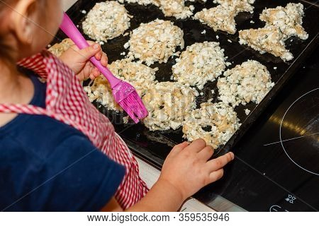 The Girl Greases Baking Oil To Make A Golden Crust. Little Girl Cooks In The Kitchen. Child Hostess