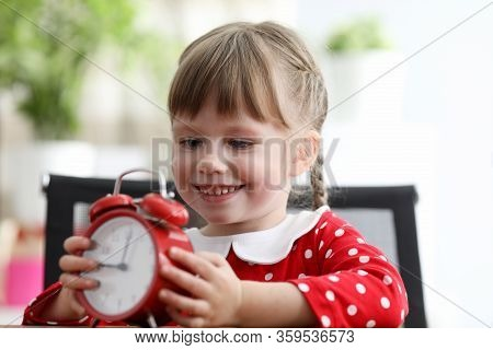 Daughter Sits At Table And Holds An Alarm Clock. Kid Gets Acquainted With Diversity World. Interesti