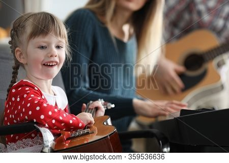 Baby Learns Play Musical Instruments With Parents. Music Teaches To Think And Live In Several Direct