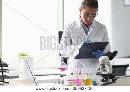Portrait Of Concentrated Woman Looking At Documents With Seriousness. Lab Assistant Writing Results