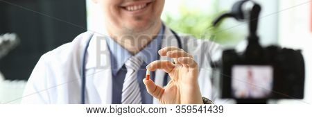 Focus On Hands Of Smiling Blogger With Capsules. Doc Advertising Medicines On Videocamera. Content M