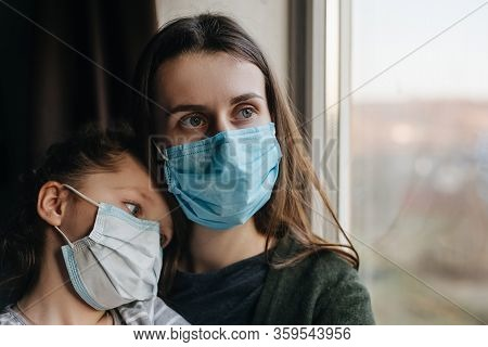 Tired Mother And Little Daughter In Medical Sterile Face Mask Sitting On Sill Looking At Window, Sad