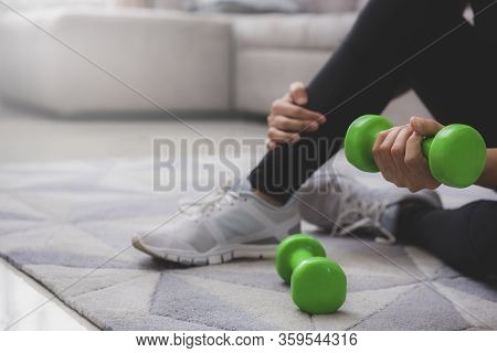 A Sporty Woman In Sportswear Is Sitting On The Floor With Dumbbells. Sport And Recreation Concept. S