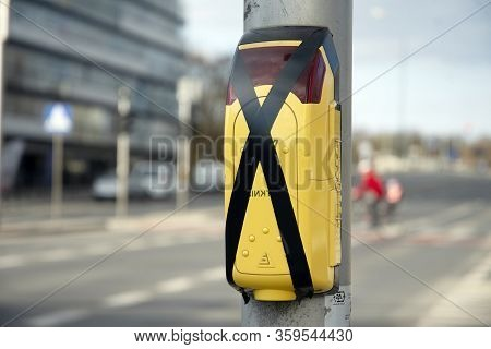 Yellow Pedestrian Crossing Sign Or Pedestrian Crossing Button Located On A Metal Pillar Next To A Pe