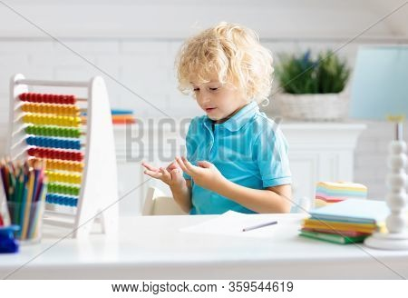 Child Doing Homework At Home. Little Girl With Wooden Colorful Abacus Doing Math Exercise Learning A