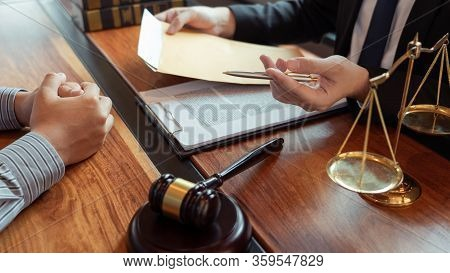 Lawyer Working With Client Discussing Contract Papers With Brass Scale About Legal Legislation In Co