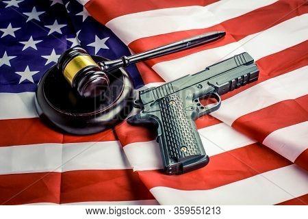 Wooden Judge Gavel And Black Color Gun Over Usa Flag.