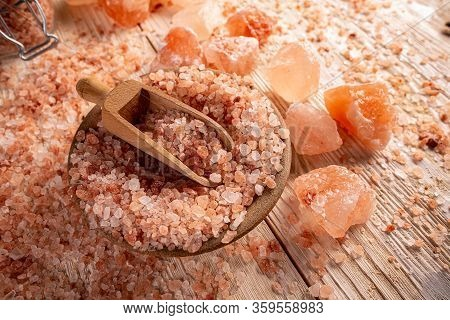 Big Crystals Of Pink Himalayan Salt In Wooden Bowl With Scoop On Wooden Board