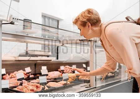 Side View Of Fasionable Lady Looking And Choosing Fresh Meat In Store. Cheerful Woman Standing And B
