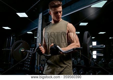 Front View Of Bodybuilder Training Biceps With Barbell. Close Up Of Muscular Handsome Sportsman With