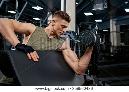 Handsome Bodybuilder Training Biceps With Dumbbell On Bench. Side Close Up Of Muscular Sportsman Wit
