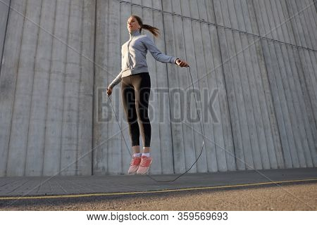 Portrait Of Fit Young Woman With Jump Rope Outdoors. Fitness Female Doing Skipping Workout Outdoors