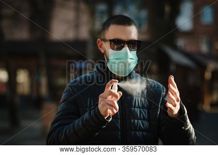 Coronavirus. Cleaning Hands With Sanitizer Spray In City. Man Wearing In Medical Protective Mask On