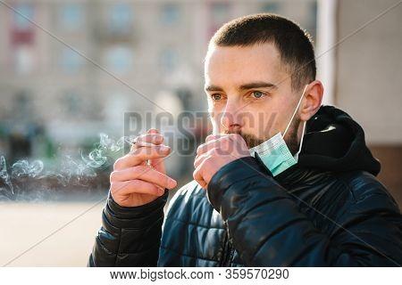 Coronavirus. Smoking. Close Up Man With Mask During Covid-19 Pandemic Coughing And Smoking A Cigaret