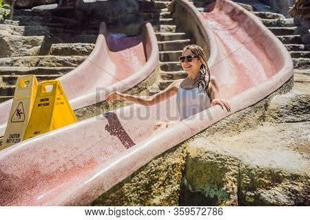 Woman On A Stone Water Slide In A Water Park. Aqua Park, Girl Slide Down On Water Slide