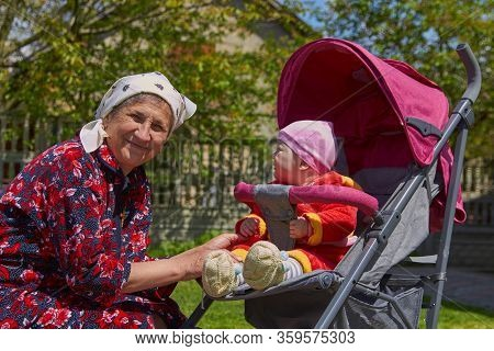 A Baby In A Stroller Looking On Senior Woman, Senior Woman With Baby Sitting In Stroller