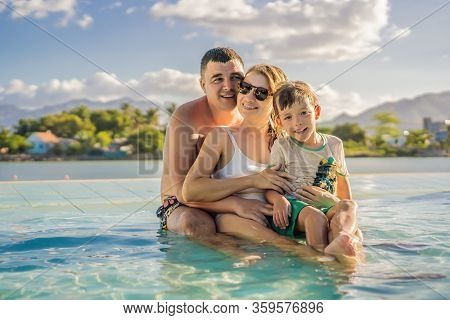 Luxury Resort Swimming Pool. Happy Family Tourists Relaxing In Holiday Retreat On Summer Travel Vaca