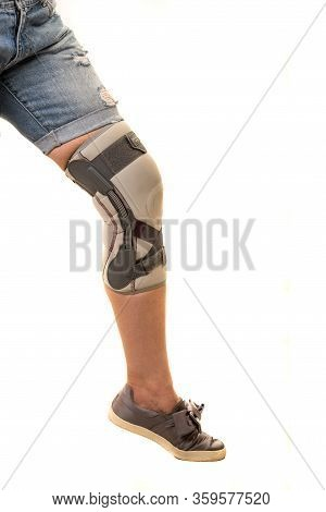 Close Up Of Woman Leg With Knee Orthosis Isolated On White Background