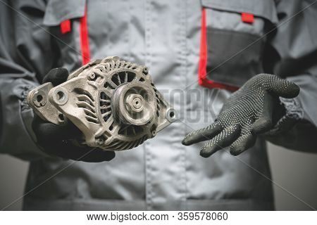 Broken Auto Generator In Auto Mechanic Hands Close Up. Replacement Of Old Car Parts.