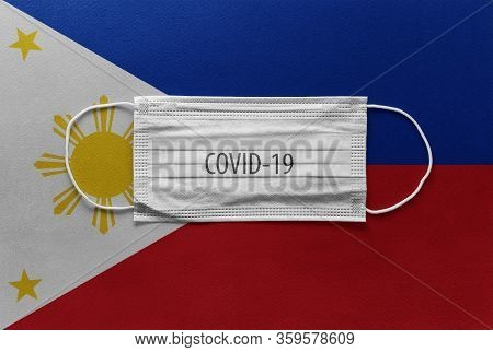 Face Medical Surgical White Mask With Covid-19 Inscription Lying On Philippines Flag. Coronavirus In