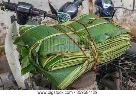 Green Banana Leaves Tied On The Back Of A Scooter. Grocery Food Transportation In South East Asia