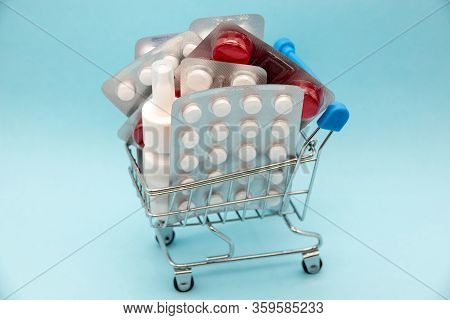 Pharmacy Medicine. Shopping Cart With Pills And Medical Supplies On Blue