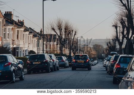 London, Uk - March 22, 2020: Car Drives Past Cars Parked On Both Sides Of A Street In Palmers Green,