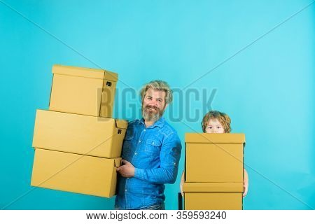 Father And Son With Boxes. Father With Son Carrying Boxes On Moving Day. Son Helping His Father Carr