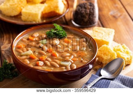 Bowl Of Tasty Bean Soup With Cornbread On A Wooden Table
