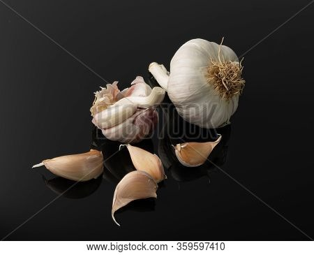 Garlic Heads And Garlic Cloves Isolated On Black Background